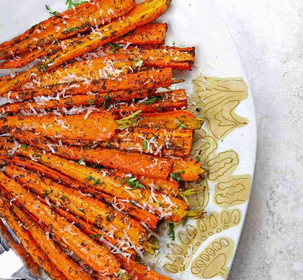 Caramelized air fryer carrots laid out on aplate topped with dill and parmesan