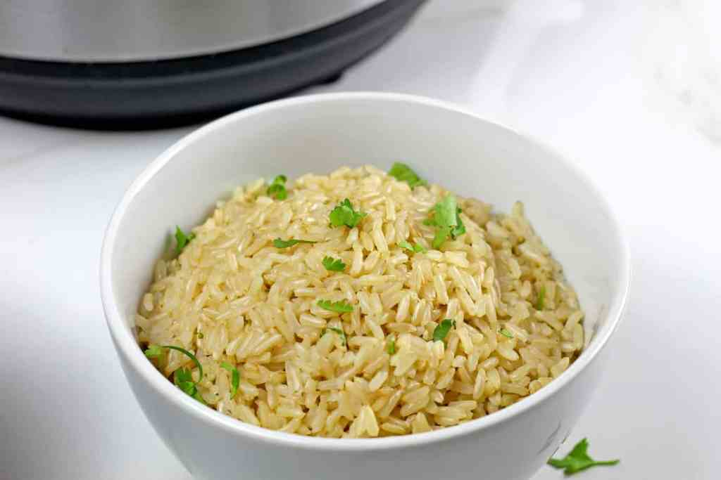 Bowl of brown instant pot basmati rice with a cilantro garnish.