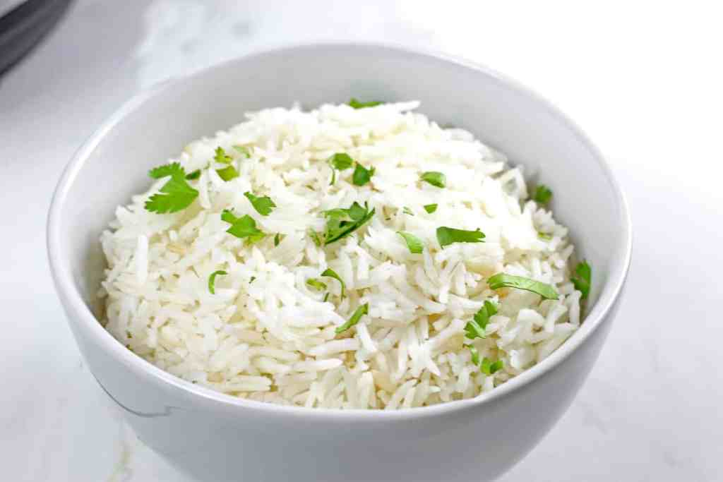 Bowl of white instant pot basmati rice with a cilantro garnish.