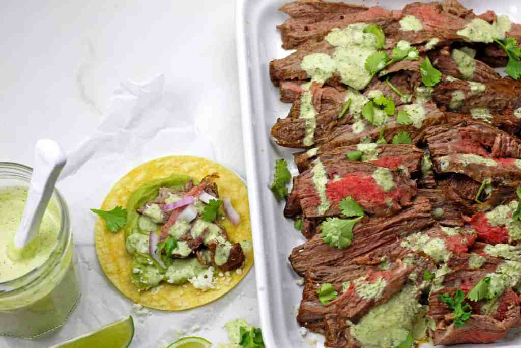 Platter of Instant Pot Carne Asada sliced up with cilantro garlic sauce and tacos on the side.