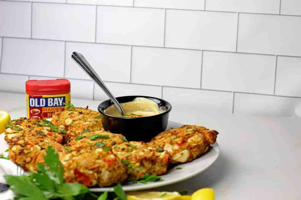 Air fryer crab cakes with a sauce on platter with a subway tile background