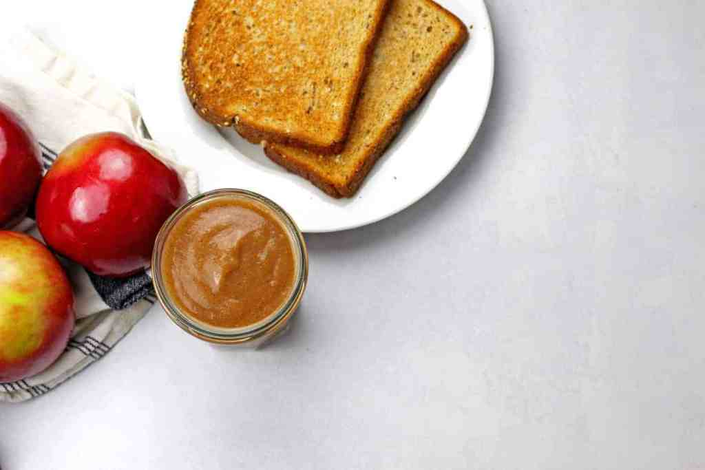 Overview from above of a jar of instant pot apple butter with whole apples and toast on the side on a white-gray background.