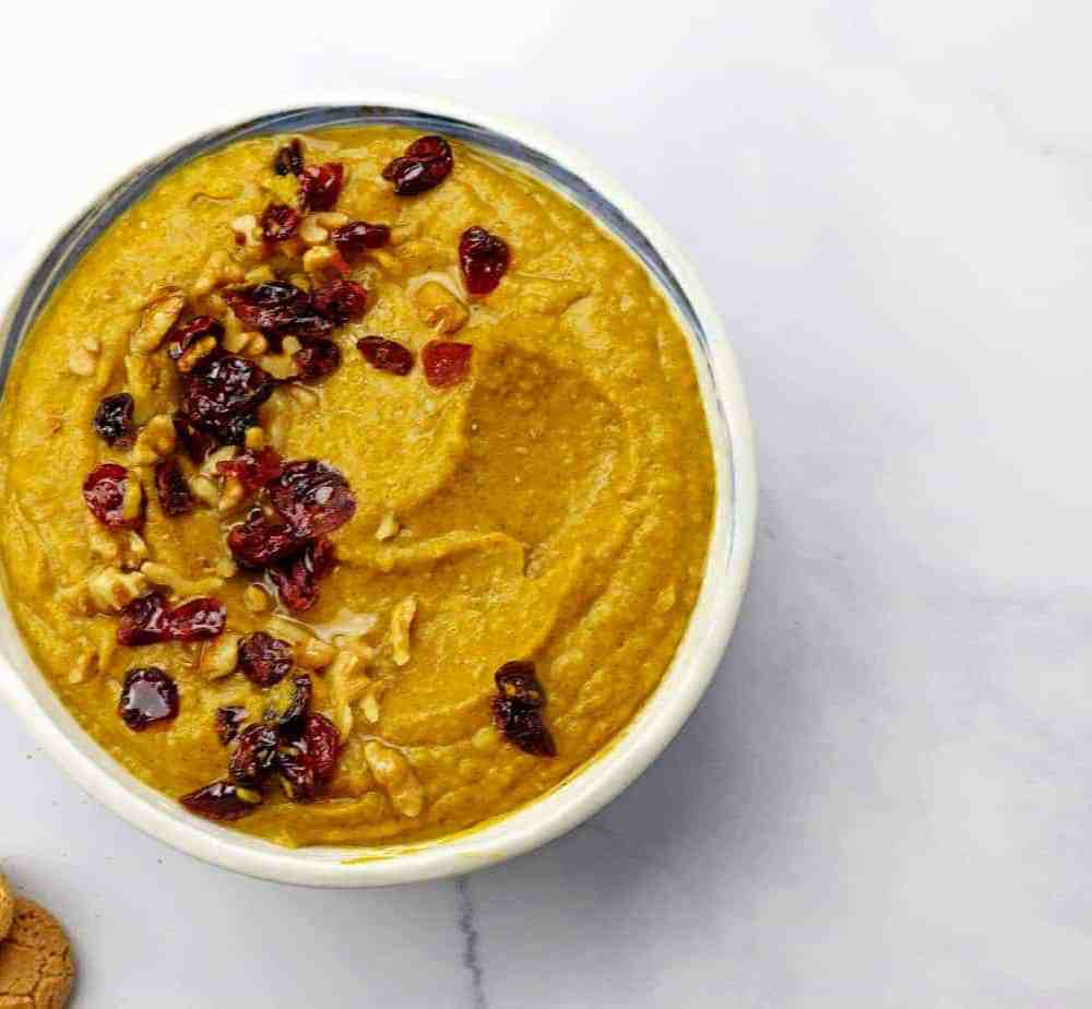 Overview of pumpkin pie hummus in a bowl on a white background with cookies crumbled on the side.