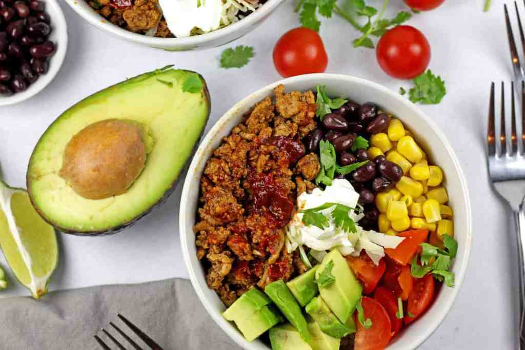 overview of turkey taco bowl with tomatoes, cilantro and avocado on the side on a white background.