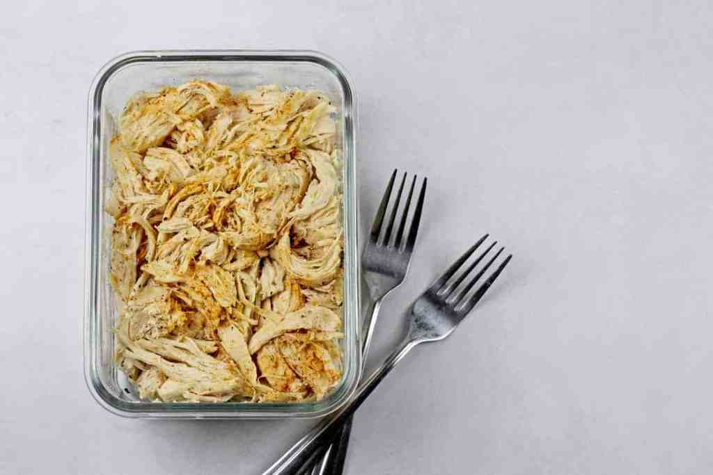 A glass dish filled with instant pot shredded chicken on a white background with two forks on the side.