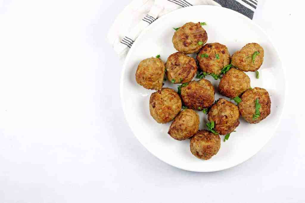 White plate of air fryer turkey meatballs on a white background with a blue and white napkin on the side.