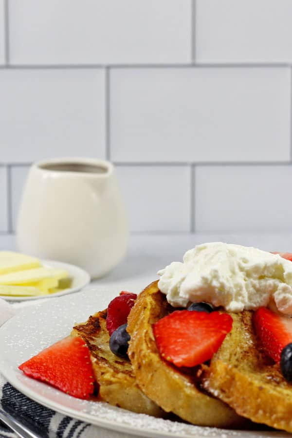 A white plate of sourdough french toast with berries and yogurt on top with a side of butter and maple syrup.