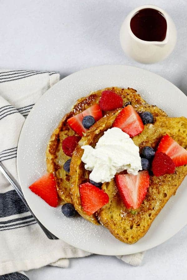 A plate of sourdough french toast with berries and yogurt on top with a side of butter and maple syrup on a white background. There is a fork and blue and white napkin on the side also.