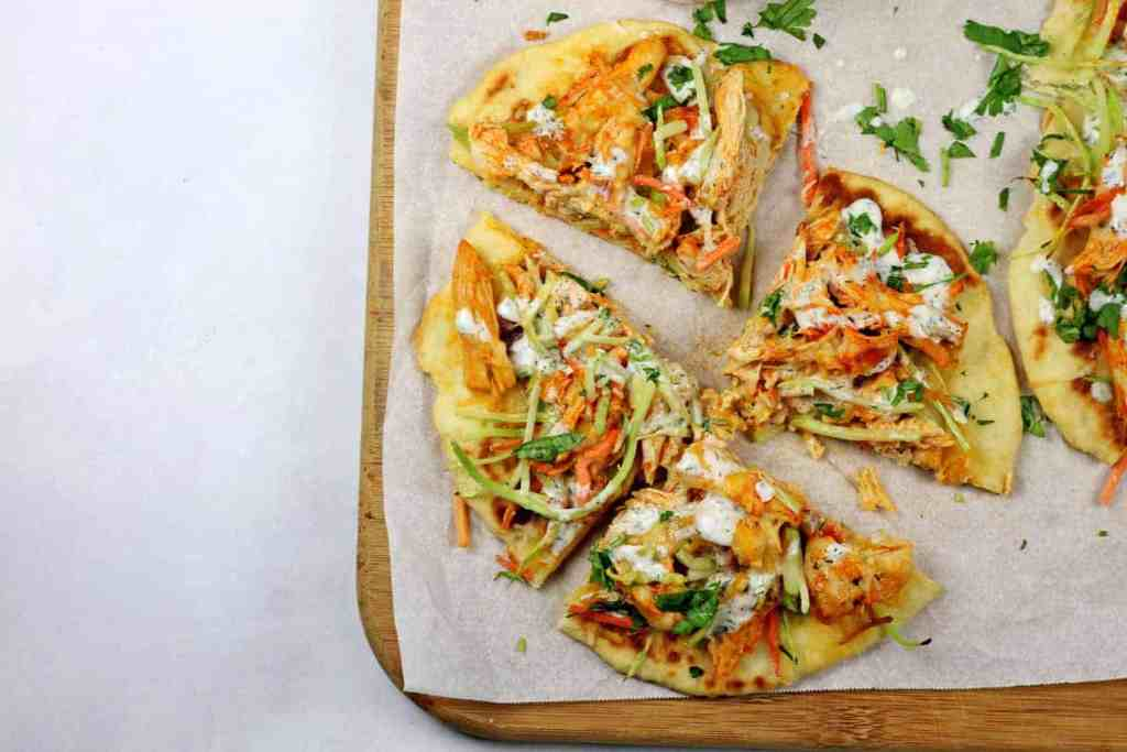 A buffalo chicken flatbread that is sliced in four pieces on a parchment paper lined cutting board on a white countertop.