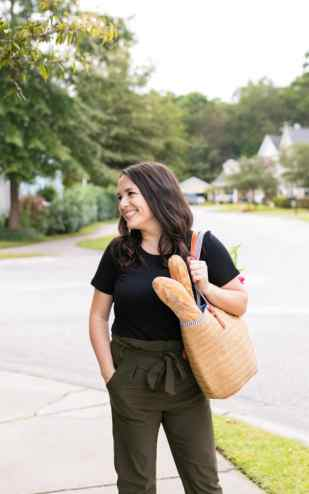 Melissa in black shirt, green pants, on a side walk smiling to her right while carrying a straw bag with bread and flowers inside.
