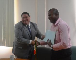 Mexico's Ambassador to Guyana, H.E Ivan Roberto Sierra recieves rice documents from GRDB official