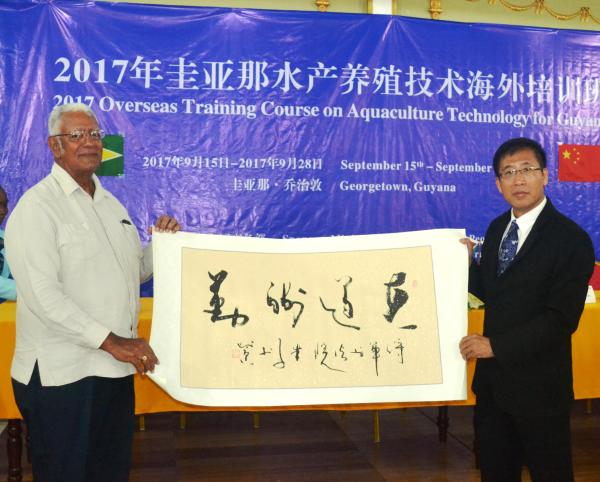 Minister Holder receives a token from Mr. Mingzhe
