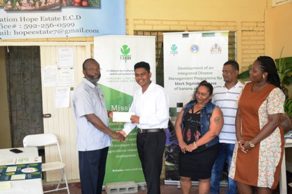 CARDI Country Representative, Dr. Cyril Roberts handing over a reward to Eion Jotis in the presence of his parents and his teacher.