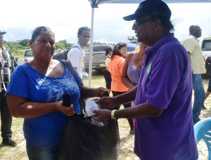 Gina Fredricks receiving the ants bait from NAREI CEO, Dr. Oudho Homenauth