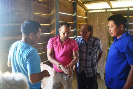 Senior Crop Extension Officer, Aaron Ramroop hands over some chemicals and ants bait to residents of Kurukabaru