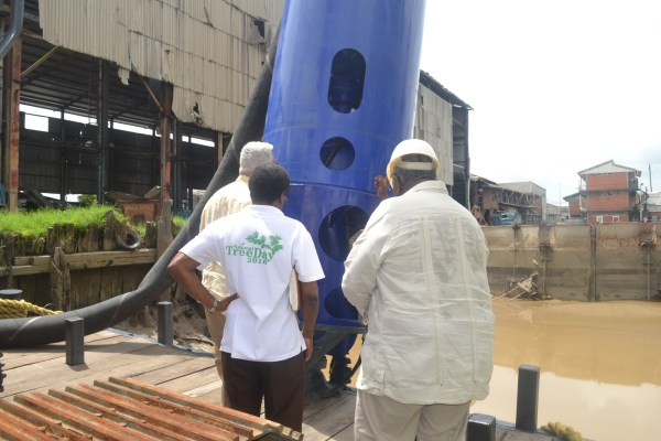 Minister Holder and other officials while taking a closer look at the dredge pump