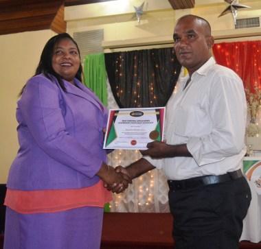One of the graduates recieving their certificate from PTCCB Registrar, Trecia Garnath