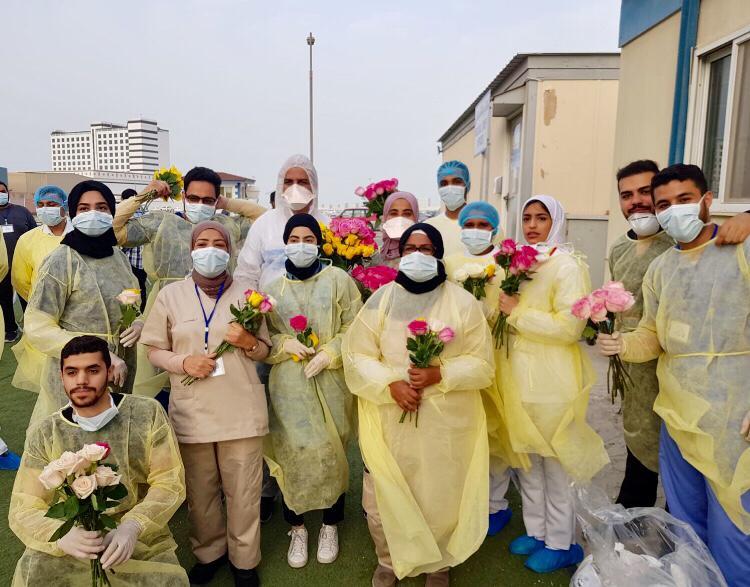 أطباء وممرضون وآخرون متطوعون مع جمعية الخالدية الشبابية يهدون الزهور للأفراد في الحجر المؤسسي في مدينة الحد. (تصوير النائب البحريني جلال كاظم)