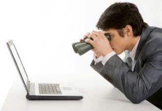 Directivo con prismáticos mirando pantalla de portátil