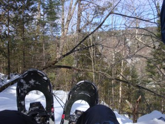 A person sitting on a big snowy hill wearing snow shoes
