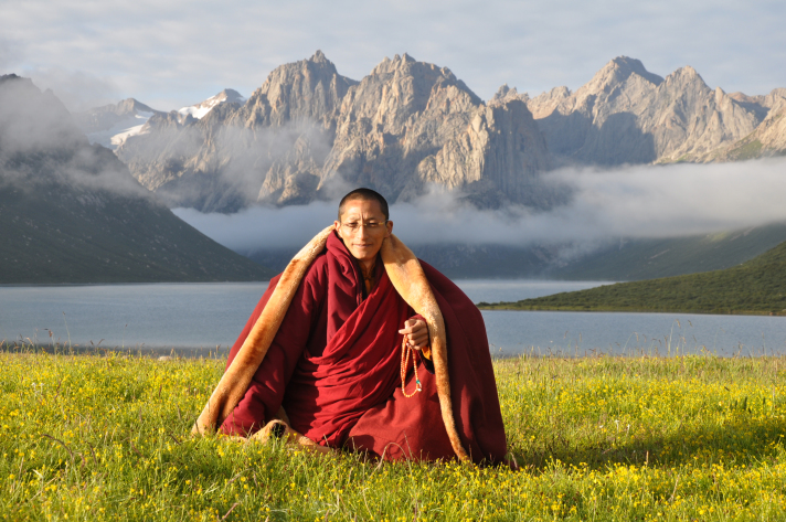 His Holiness Gyalwai Nyugu Rinpoche sitting in a field with mountains behind him