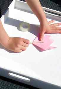 Child Folding Paper Square In Half