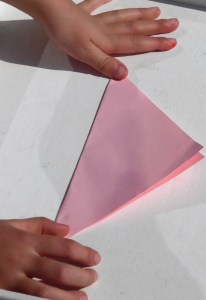 Child Folding Paper Square In Half
