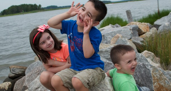 Eden, Judah, and Levi sitting on large stones near the bay shore.