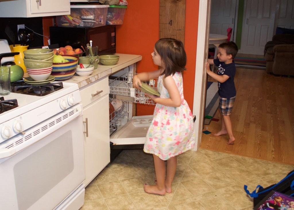 Eden emptying the dishwasher