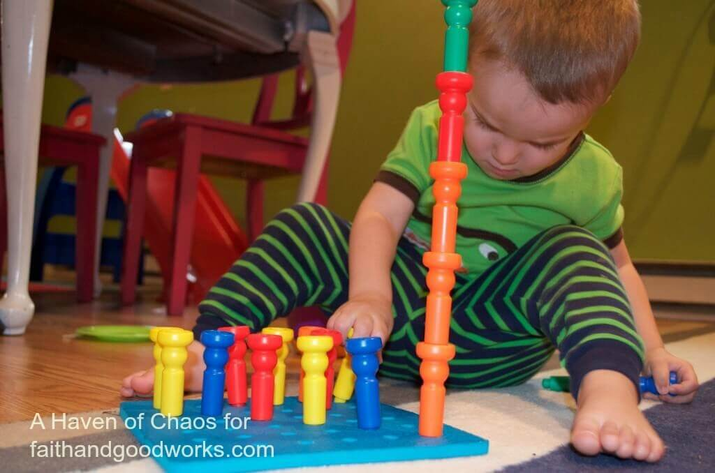 Sarah's two-year-old son playing with tall-stacker pegs and pegboard
