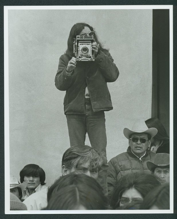 "Buddy Mays using a camera in a crowd of people. Written on the back: ""Gallup, NM Navajo Press photographer at work.""  American Heritage Center, Photofile: Indian - Tribe - Navajo."