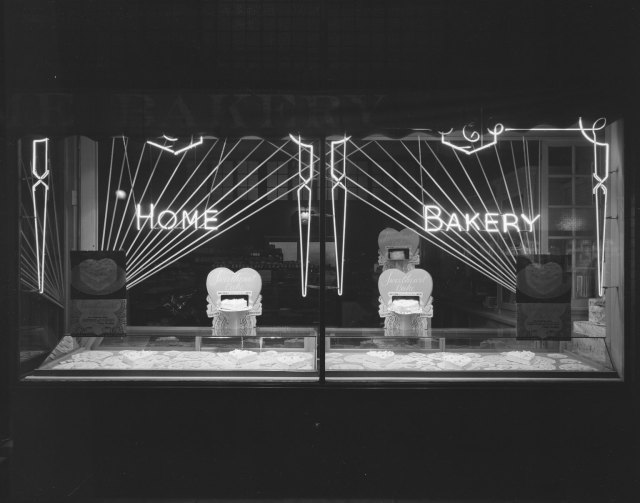 Home Bakery window display, Laramie, Wyoming, February 1941, night-time photography, neon lights lighting a collection of heart shaped cakes.  Home Bakery window display, 1941, University of Wyoming, American Heritage Center, Ludwig Svenson Collection, negative number 33857.1