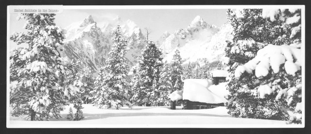 Winter solitude in the Tetons showing a cabin covered in snow with the Teton Mountains in the background. Taken from the back: Snowbound in the Tetons. Fritiof Fryxell Papers, Collection #1638, Negative #22587. University of Wyoming, American Heritage Center.