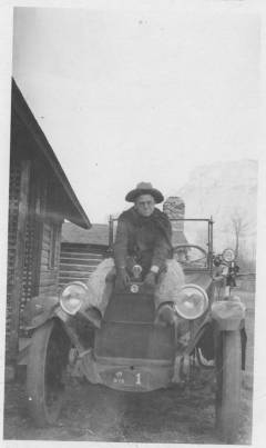 Jacob M. Schwoob sitting on the hood of an old automobile, displaying his number 1 Wyoming license plate.