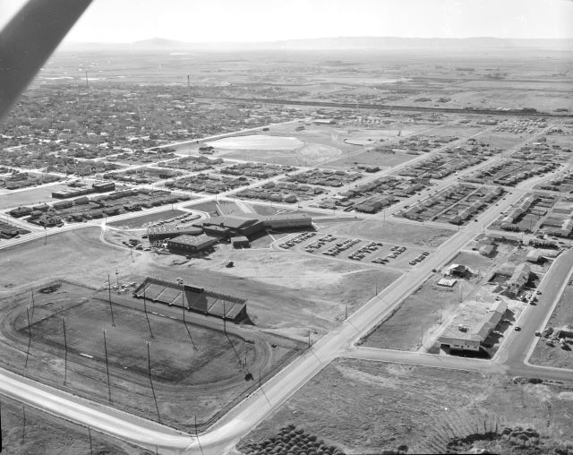 Black and white photo looking southwest toward the downtown area and showing Deti Stadium, named in honor of Coach John Deti Sr. From this view there are houses and buildings visible in much of the shot, including West Laramie.