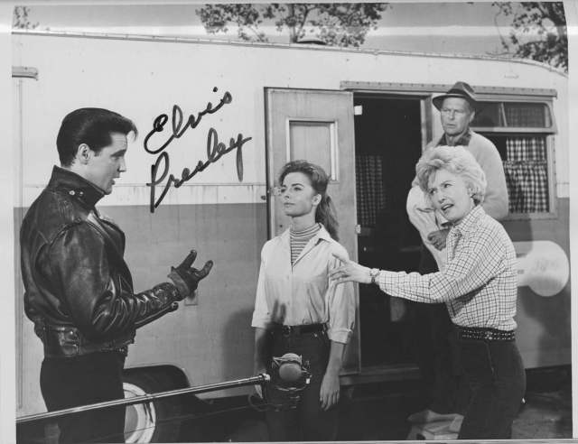 Black and white photo of 4 people standing in front of a trailer with a boom microphone visible in front of the people. Elvis Presley is on theleft wearing a leather jacket, with Joan Freeman and Barbara Stanwyck standing opposite him and Leif Erickson standing behind Barbara Stanwyck. Next to Elvis is a signature of his full name.