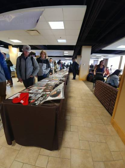 Several students walk down a row of tables in the hallway of the student union viewing an exhibit on display.
