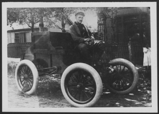 man driving an old automobile