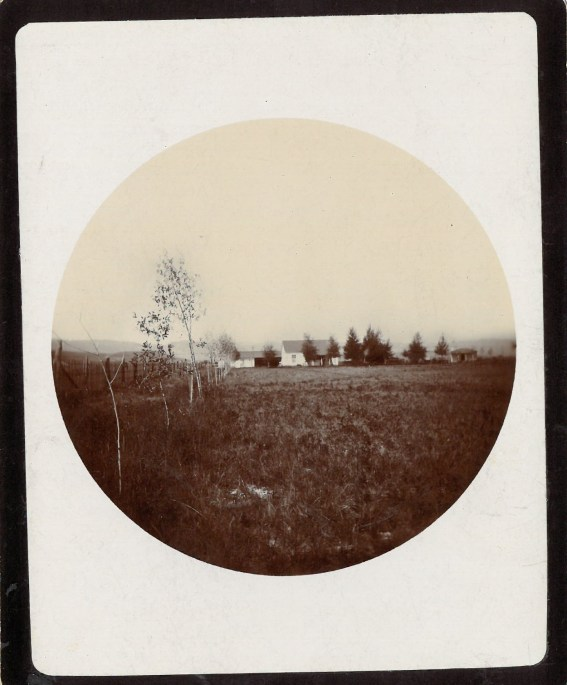 circle photo of white house with grassland and sparse trees throughout property.