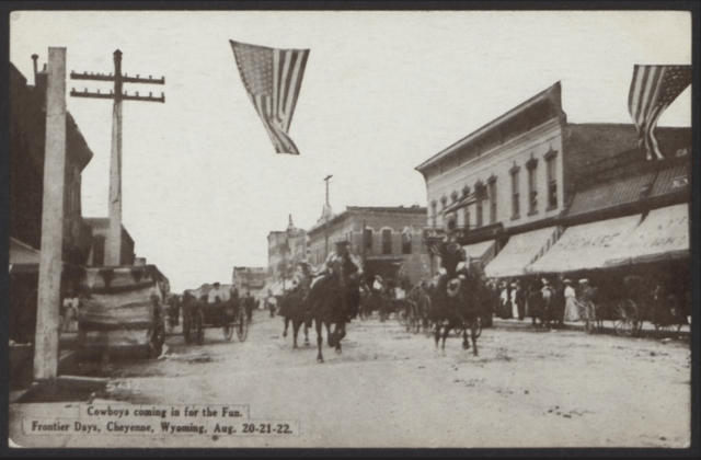 downtown street with buildings, flag, wagon and people riding horses
