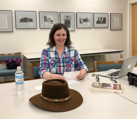 woman posing sitting with hat, computer and book on desk.