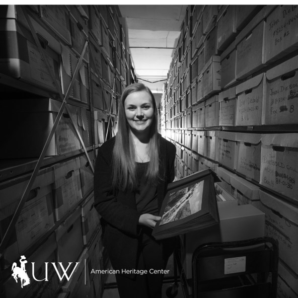 black and white image; one person smiling in hall of archives shelves. person holding collection