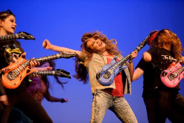 three women with fake plastic guitars