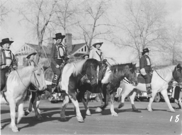 women on horses in street