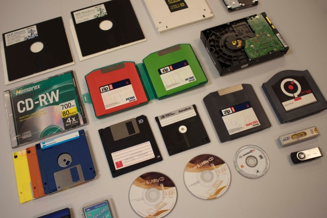 Assortment of obsolete and current storage media for digital files including floppy disks, Zip drives, CDs, and flash drives. Files on these disks are transferred to readable formats by the American Heritage Center's Born Digital unit.