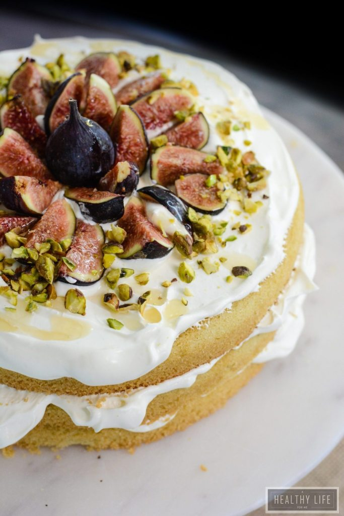 Gluten Free Fig and Cream Cake Coconut cream is layered between three perfectly light and moist egg white cakes. Then topped with fresh seasonal figs, crumbled pistachio and a drizzle of golden honey | ahealthylifeforme.com