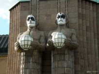 Helsinki Central railway station lamp holding statues wearing Kiss masks