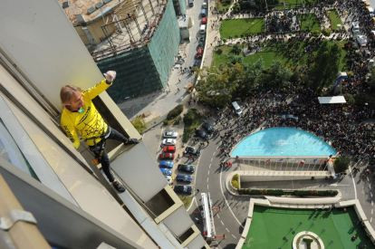 French urban climber Alain Robert, also known as the French Spiderman, celebrates after reaching the top floor of a 22-storey hotel building in Bucharest October 14, 2011. REUTERS/Flanco/Handout