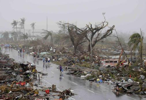 Residents walked passed damaged houses in Tacloban City, after it was devastated by Typhoon Haiyan that slammed into Tacloban City, Leyte province Philippines as seen on Saturday, Nov. 10, 2013. AP Phoro/Bullit Marquez.