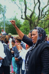 A woman raises her fist as the crowd sang the national anthem.
